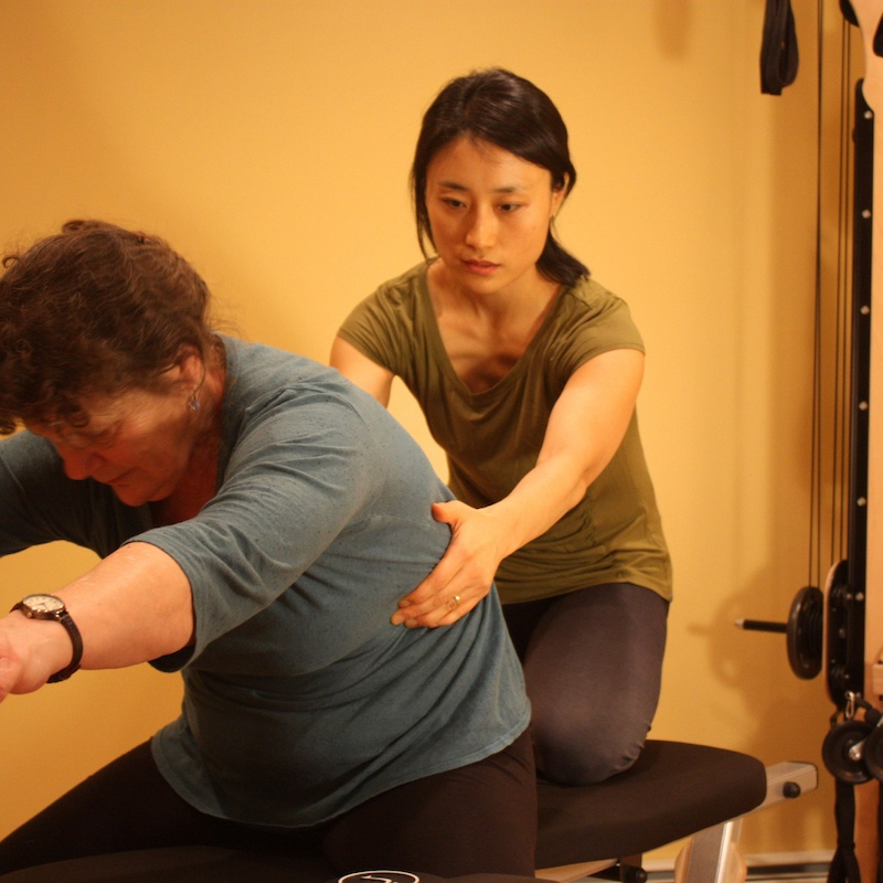 Certified Gyrotonic Instructor Kyung-sun Baek works with a client to help reduce her back pain.