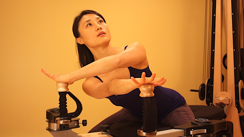 Personal Fitness Trainer Kyung-sun Baek doing a spinal twist movement on a Gyrotonic Pulley Tower Exercise Machine
